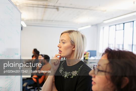 Focused businesswomen brainstorming at whiteboard in office - p1023m2017242 by Sam Edwards