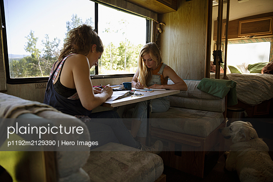 Young women planning trip at table in motorhome - p1192m2129390 by Hero Images