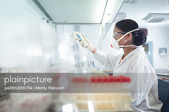 Female scientist researcher wearing mask and using pipette at workstation in research laboratory - p429m2200754 by Monty Rakusen