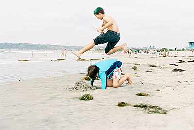 Side view of boy jumping over brother kneeling on shore at beach - p1166m1485344 by Cavan Images