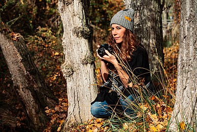 Madrid, Spain. Young woman photographing in a forest and walking with her dog. - p300m2276052 von Manu Reyes