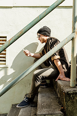 Young man surfing net through smart phone sitting on steps - p300m2290446 by VITTA GALLERY