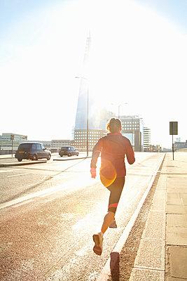 Woman running on city street - p429m800813f by Moof