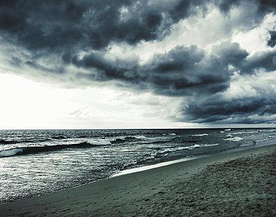 Gewitterwolken und Brandung an einem Strand - p586m891087 von Kniel Synnatzschke