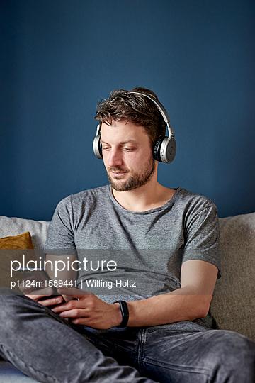 Junger Mann mit Kopfhörer und Smartphone - p1124m1589441 von Willing-Holtz