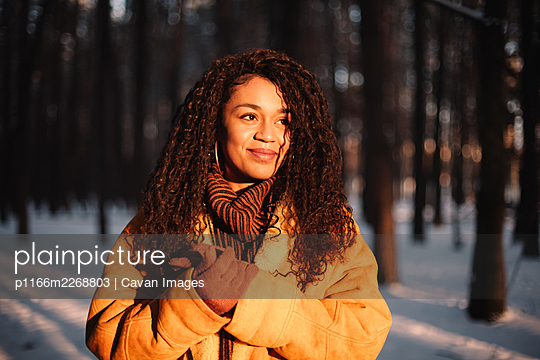 Happy young woman looking at sun standing in park during winter - p1166m2268803 by Cavan Images
