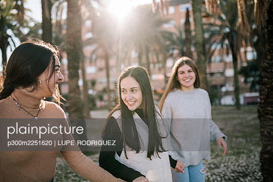 Happy female friends holding hands while walking on footpath in park - p300m2251620 by LUPE RODRIGUEZ