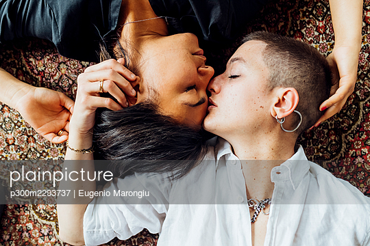 Affectionate girlfriends lying on carpet at home - p300m2293737 by Eugenio Marongiu
