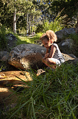 Curly-haired girl on the riverbank - p1640m2246806 by Holly & John