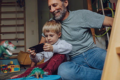 Father watching son playing games on smart phone at home - p300m2266707 by Mareen Fischinger
