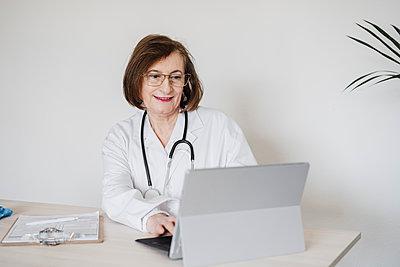 Senior doctor woman using digital tablet at desk against wall - p300m2273973 by Eva Blanco