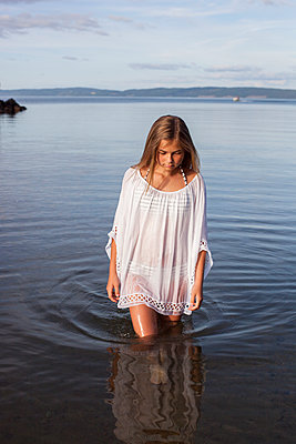 Teenage girl walking in water - p312m1470282 by Christina Strehlow