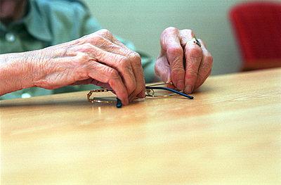 Senior woman holding her glasses - p8960127 by Stijn Rademaker