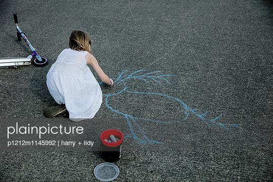 Mädchen malt mit Straßenkreide einen Vogel auf den Asphalt - p1212m1145992 von harry + lidy