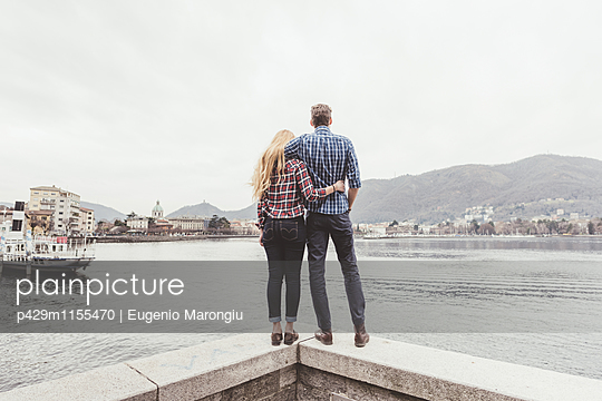 Rear view of young couple standing on harbour wall looking out, Lake Como, Italy - p429m1155470 by Eugenio Marongiu