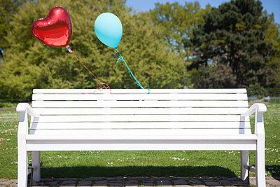 Zwei Luftballons an Parkbank - p045m1149705 von Jasmin Sander