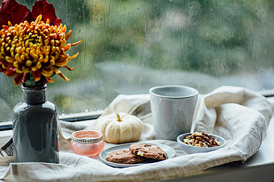 Cup of coffee, cookies and autumnal decoration on window sill - p300m2080209 von Jean Schwarz
