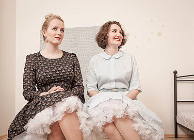 Young women in vintage dresses sitting side by side - p300m929811f by Dieter Schewig
