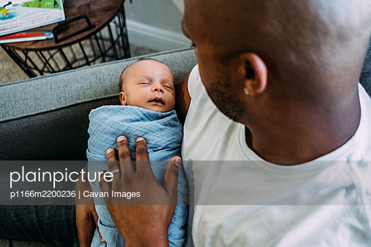 newborn baby sleeping in fathers arms - p1166m2200236 by Cavan Images