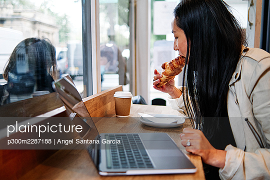 Woman eating croissant in front of laptop at cafe - p300m2287188 by Angel Santana Garcia