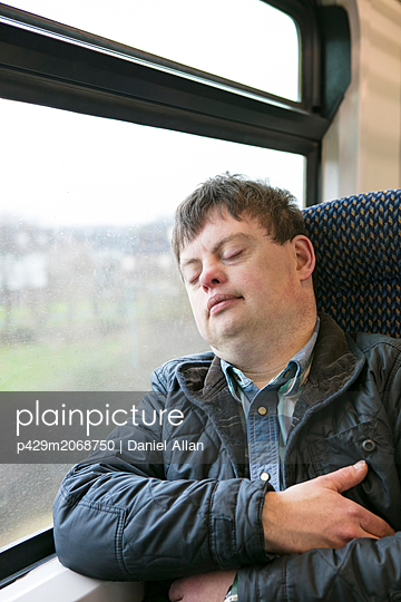 Man with down syndrome sleeping on train - p429m2068750 by Daniel Allan