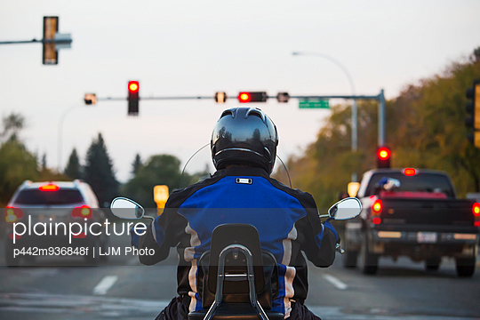 Man on a motorcycle in traffic; Edmonton, Alberta, Canada