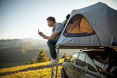 Serene man camping, relaxing at SUV rooftop tent in sunny, idyllic field, Alberta, Canada - p1192m2016507 by Hero Images