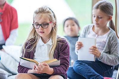 Schoolgirls reading books in school break room - p300m2005296 by Fotoagentur WESTEND61