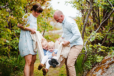 Parents swinging children in blanket - p312m2237244 by Anna Johnsson