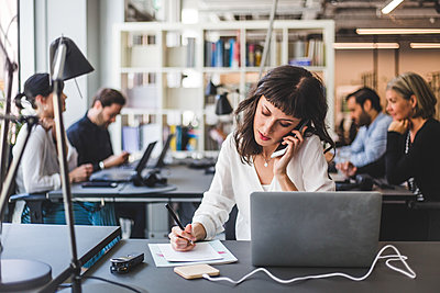 Businesswoman talking on mobile phone while working at desk in creative office - p426m2033834 by Maskot