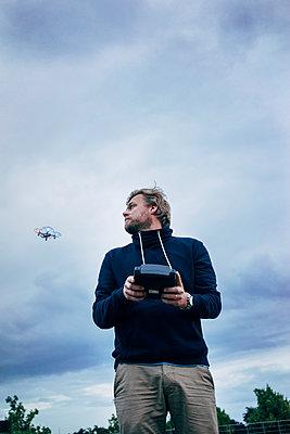 Mann steuert eine Drohne - p819m1042471 von Kniel Mess