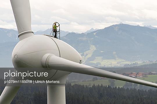 Mann auf Windkraftanlage vor Alpenpanorama - p1079m1185018 von Ulrich Mertens