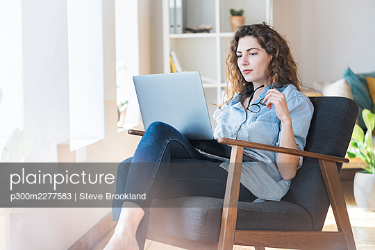 Thoughtful young woman holding eyeglasses while looking at laptop on chair at home - p300m2277583 by Steve Brookland