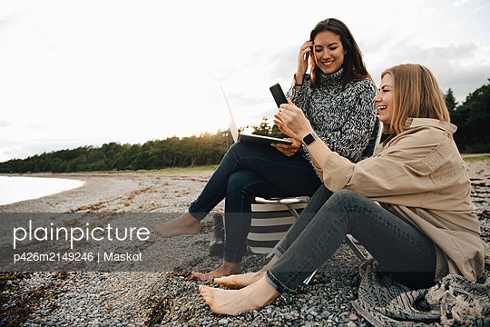 Happy friends looking at smart phone while sitting on shore at beach against sky - p426m2149246 by Maskot