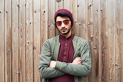 Portrait of serious bearded man in purple knit hat and shirt with arms crossed wearing sunglasses over wooden background - p300m2083393 by Ivan Gener