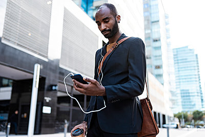 Yung businessman looking at smartphone outdoors - p300m2160666 von Josep Suria