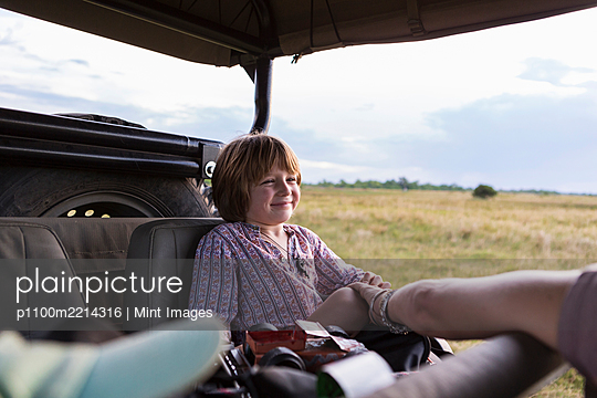 A five year old boy on safari, in a jeep in a game reserve - p1100m2214316 by Mint Images