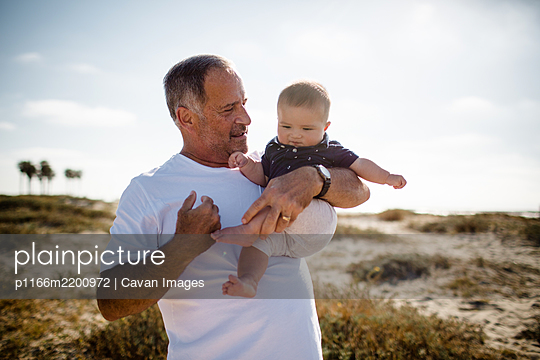 Grandfather Holding Grandson While Standing on Beach - p1166m2200972 by Cavan Images