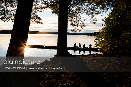 Young woman on the pier of a lake in Dalarna Sweden - p352m2119894 by Lena Katarina Johansson
