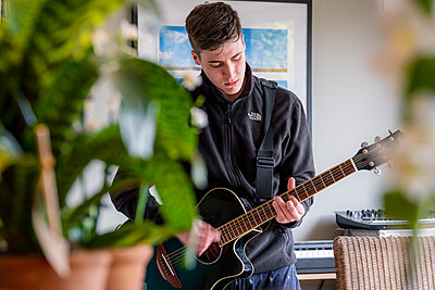Young man practicing guitar in the kitchen, stay at home due to Covid-19 - p1057m2185216 by Stephen Shepherd