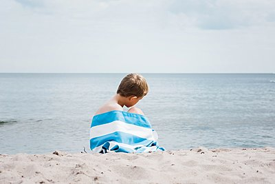 young boy sat wrapped in a striped towel alone on the beach - p1166m2205698 by Cavan Images