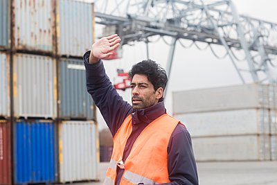 Man wearing reflective vest working at container port - p300m1563283 by Sigrid Gombert