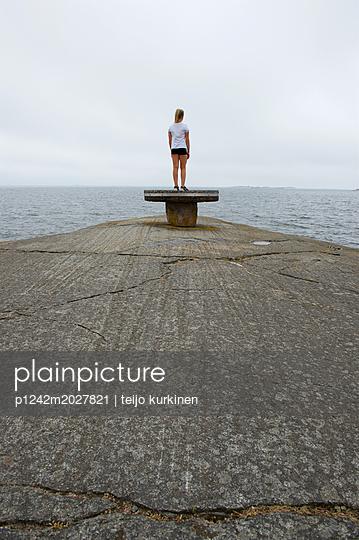 Mädchen auf einem Poller am Pier von Hanko - p1242m2027821 von teijo kurkinen