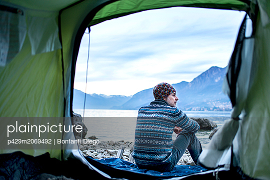 Man camping on lakeside, view from inside tent, Onno, Lombardy, Italy - p429m2069492 by Bonfanti Diego