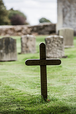 A samll wooden cross in a grassy garveyard in a rural church. - p1057m2020705 by Stephen Shepherd