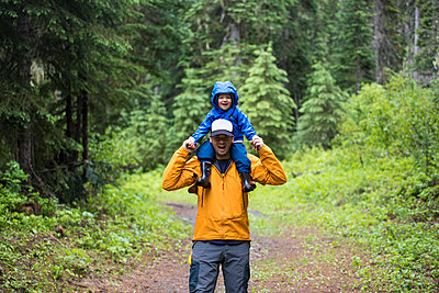 Father carrying son on shoulders during a hike through the forest. - p1166m2094935 by Cavan Images
