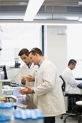 Scientists talking at scale in laboratory - p1192m1145633 by Hero Images