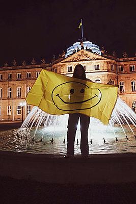 Deutschland, Stuttgart, Frau mit Smiley Flagge auf Brunnen - p1301m2196931 von Delia Baum