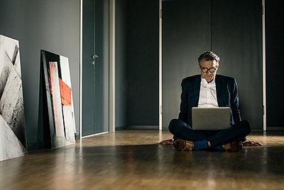 Mature businessman using laptop on office floor - p300m2004675 von Joseffson