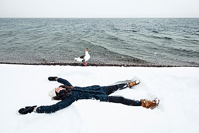 Grey goose and young woman at Lake Starnberg in winter - p300m2084015 by Wilfried Feder